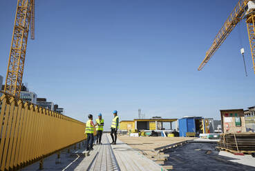 Male and female engineers discussing at construction site against blue sky - MASF15985