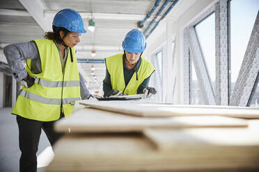 Female architects discussing over blueprint at construction site - MASF15988