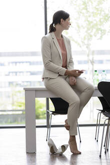 Young businesswoman with smartphone having a break in office - BMOF00107