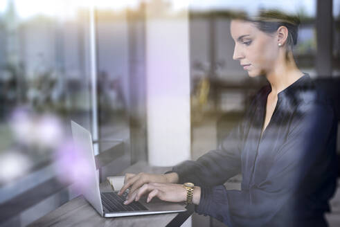 Businesswoman using laptop behind windowpane in a cafe - BMOF00125
