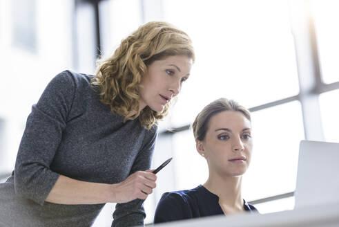 Two women working on laptop in office - BMOF00134