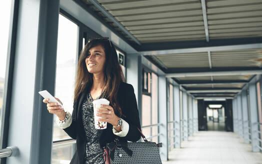 Happy woman looking away while standing on footbridge - CAVF70975