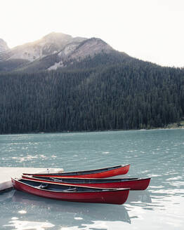 Canoe moored in lake by mountain against clear sky - CAVF71011