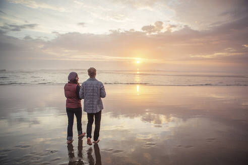 Rear view of couple walking at beach against sky during sunset - CAVF71083