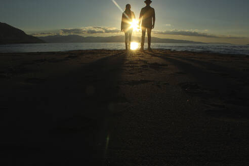 Silhouette couple standing on sand by lake during sunset - CAVF71203