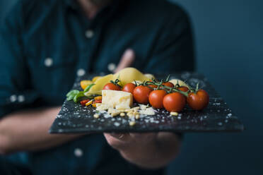 Man holding platter with cheese and tomatoes - JOSF04113