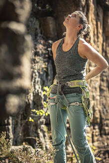 Woman preparing to climb, looking up on climbing wall - MSUF00073