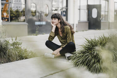 Young smiling woman wearing silk blouse and sitting on the ground - KNSF06967