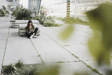Young smiling woman sitting on the ground and using tablet - KNSF06970