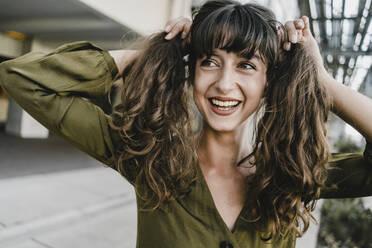 Portrait of smiling brunette woman, holding braids - KNSF06982