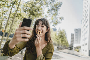 Portrait of brunette woman, taking a selfie, rabbit teeth with french fries - KNSF06985