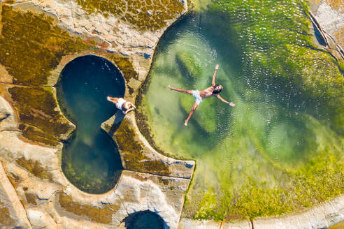 Aerial view of couple floating at figure eight pools at Sydney's Royal National Park, Australia. - AAEF06104