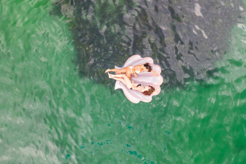 Aerial view of two attractive girls floating at Gordons Bay with inflatable, Sydney. Australia. - AAEF06113