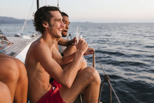 Young men enjoying champagne on sailboat, Italy - CUF54187