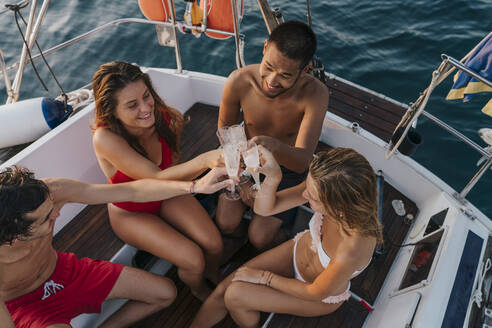 Friends toasting with champagne on sailboat, Italy - CUF54190