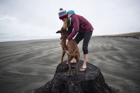 Playful woman standing with dog on log at beach against sky - CAVF72445