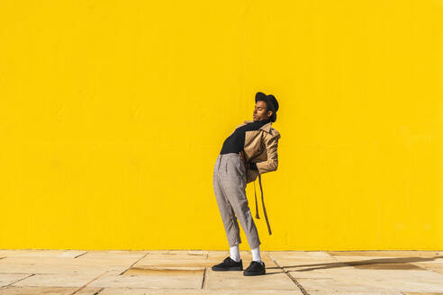 Young man dancing in front of yellow wall - AFVF04527