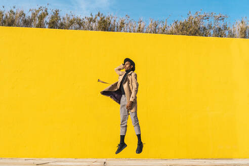 Young man dancing in front of yellow wall, jumping mid air - AFVF04530