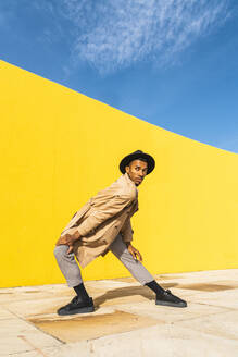 Young man dancing in front of yellow wall - AFVF04539