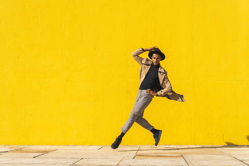 Young man dancing in front of yellow wall, jumping mid air - AFVF04542