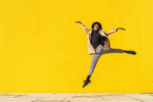 Young man dancing in front of yellow wall, jumping mid air - AFVF04548