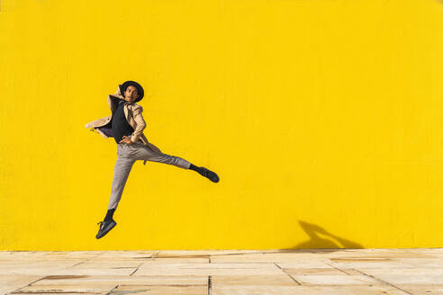 Young man dancing in front of yellow wall, jumping mid air - AFVF04551