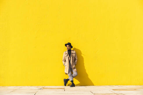Young man dancing in front of yellow wall - AFVF04557