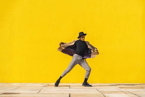 Young man dancing in front of yellow wall - AFVF04560