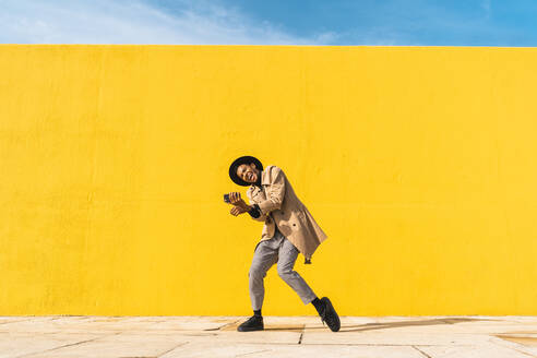 Young man dancing in front of yellow wall, taking selfies - AFVF04575