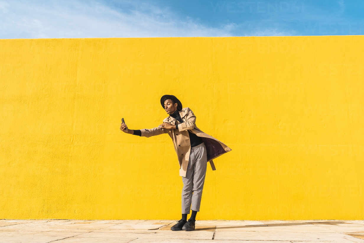 Young man dancing in front of yellow wall, taking selfies - AFVF04578 - VITTA GALLERY/Westend61