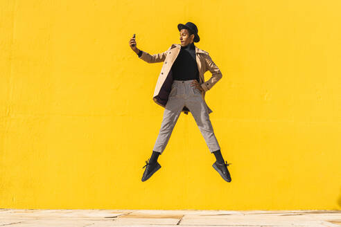 Young man dancing in front of yellow wall, taking selfies - AFVF04581