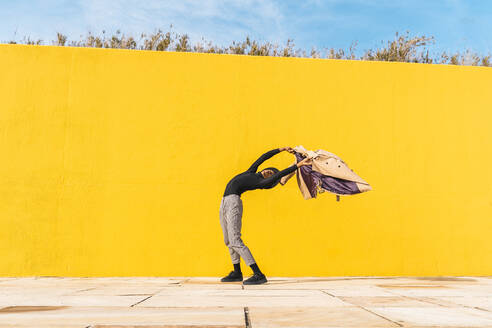 Young man dancing in front of yellow wall - AFVF04584