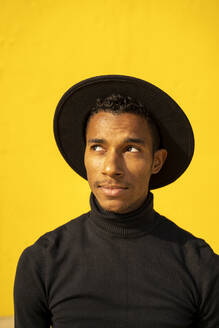 Portrait of young man, wearing black in front of yellow wall, looking up - AFVF04587