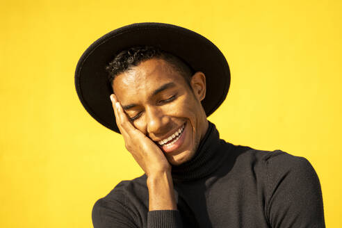 Portrait of young man, wearing black in front of yellow wall, hand on face - AFVF04590