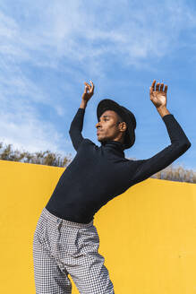 Young man with black hat, dancing in front of yellow wall - AFVF04593