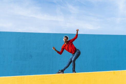 Young man with headphones, listening music, dancing on yellow wall - AFVF04602