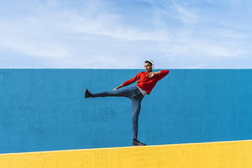 Young man with headphones, listening music, dancing on yellow wall - AFVF04605