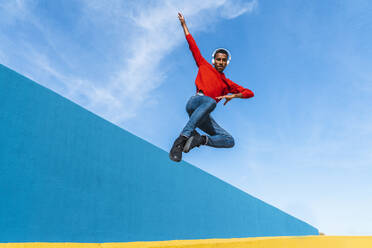 Young man with headphones, listening music, dancing on yellow wall - AFVF04614