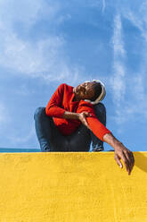 Young man with headphones, listening music, dancing on yellow wall - AFVF04617