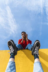 Young man with headphones, dancing for person, leaning on yellow wall - AFVF04620
