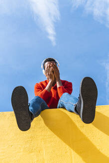 Young man with headphones, sitting on yellow wall, listening music - AFVF04623