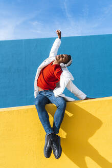 Young man with headphones, listening music, dancing on yellow wall - AFVF04626