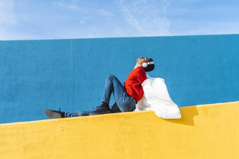 Young dancer sitting on yellow wall, listening music - AFVF04629