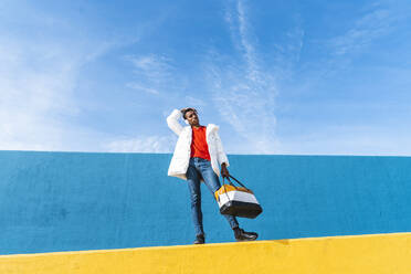 Young trendy man standing on yellow wall, listening music - AFVF04632