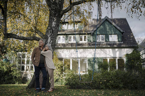 Senior couple in garden of their home in autumn - GUSF02972