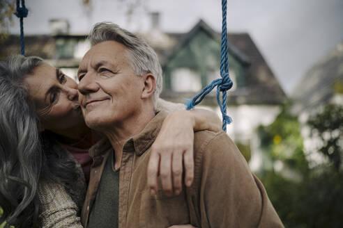Happy woman hugging an kissing senior man on a swing in garden - GUSF02978