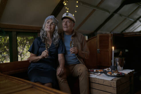 Senior couple having a candlelight dinner on a boat in boathouse - GUSF02981