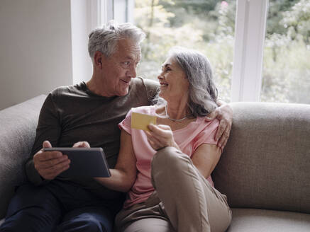 Happy senior couple relaxing on couch at home using tablet for online shopping - GUSF03002