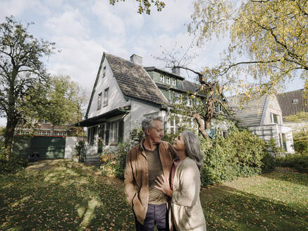Senior couple in garden of their home in autumn - GUSF03017