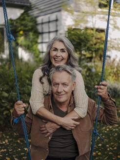 Happy woman embracing senior man on a swing in garden - GUSF03020